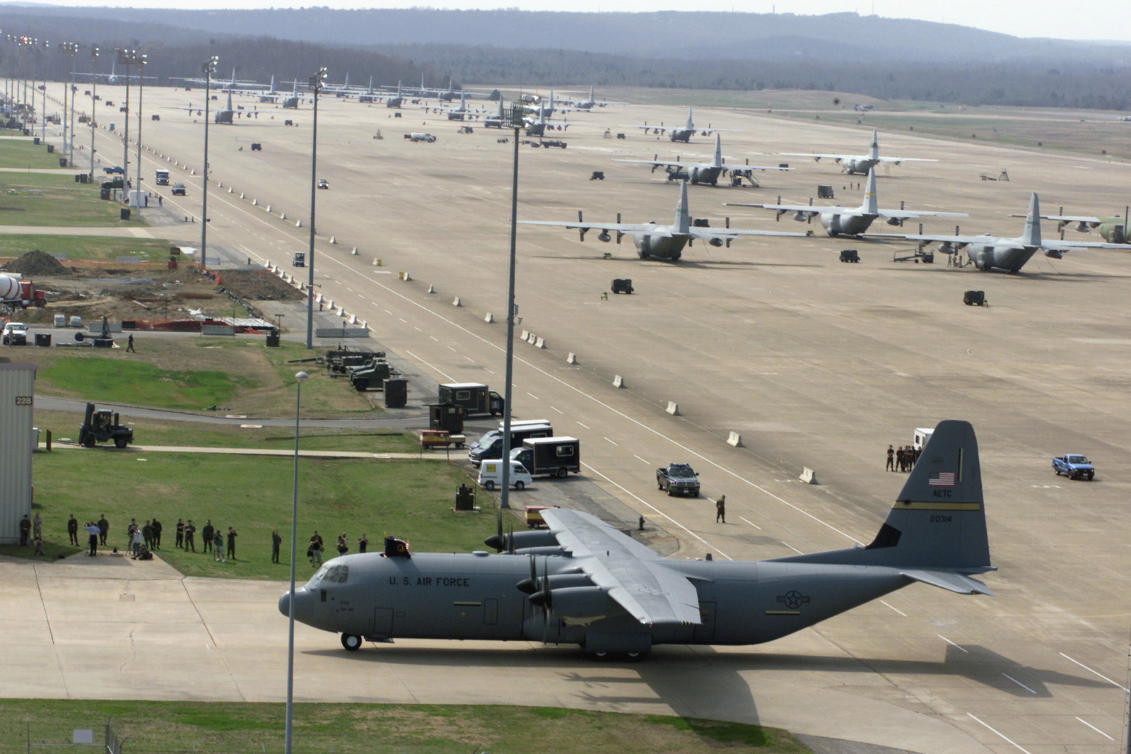 A group of onlookers are on hand to witness as a US Air Force (USAF) C-130J Hercules, Tactical Transport Aircraft taxies into position at its new home at Little Rock Air Force Base (AFB), Arkansas (AR)