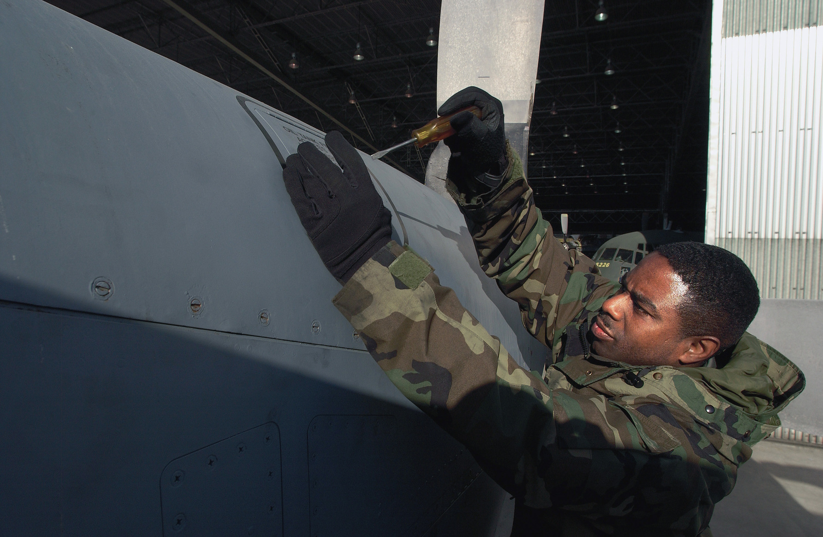 US Air Force (USAF) Technical Sergeant (TSGT) Fonzell Marsh, a Crew CHIEF with the 37th Airlift Squadron (AS), performs a series of maintenance checks on a C-130 Hercules cargo aircraft in Lisbon, Portugal (PRT)