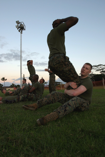 US Marine Corps (USMC) Corporal (CPL) Scott, (front, standing), Headquarters and Service Battalion (H&S BN), Marine Forces Pacific (MARFORPAC), Camp H. M. Smith, Hawaii (HI), performs vertical sit-ups as Lance Corporal (LCPL) Harlaman (front, seated), H&S BN, MARFORPAC, holds his legs, while participating in a unit wide conditioning exercise to enhance their combat readiness and improve their personal physical fitness