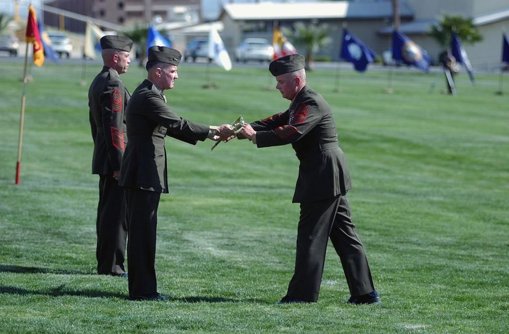 US Marine Corps (USMC) Major General (MGEN) Thomas S. Jones (center), Commanding General (CG), Training and Education Command, Marine Corps Combat Development Command (MCCDC), Marine Corps Base (MCB) Quantico, Virginia (VA), hands a USMC Non-Commissioned Officer (NCO) sword to USMC Sergeant Major (SGM) James Ricker (right), (incoming) Marine Corps Air Ground Combat Center (MCAGCC) Sergeant Major (SGTMAJ), during the Post, Relief, and Retirement Ceremony for USMC SGM Stephen Clarke (left), (outgoing) MCAGCC Sergeant Major (SGTMAJ), held aboard Marine Air Ground Task Force (MAGTF) Training Compound, Twenty-nine Palms, California (CA)