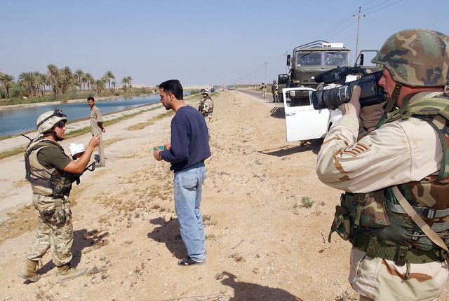 During the afternoon patrol along the perimeter of Camp Babylon, Polish Soldiers pull over a Volkswagen and closely question two Iraqi civilians. The two are suspected of having illegal weapons. US Air Force (USAF) STAFF Sergeant (SSGT) Nathan Germann, Videographer, Hill Air Force Base (AFB), Utah (UT), documents the event during Operation IRAQI FREEDOM