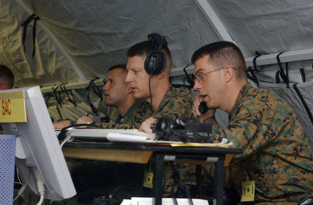 US Marine Corps (USMC) Lieutenant Colonel (LTC) Mark Workman (second from right), Tactical Operations Center (TOC) and Major (MAJ) Tim Fawcett (right), SENIOR Air Director, both with 1ST Marine Aircraft Wing (MAW), use a computer to assess flight line issues from their duty station inside the 1ST MAW revetment area at Yecheon Airport (YEC), Yecheon County, Gyeongsangbuk-do Province, Republic of Korea (KOR), while participating in Korea Field Training Exercise 2004 (FTX 04). Korea FTX 04 is part of a Reception Staging Onward Moving and Integration (RSO&I) theater-level training exercise designed to test the 1ST MAWs ability to rapidly deploy its command and control function to the Korean...