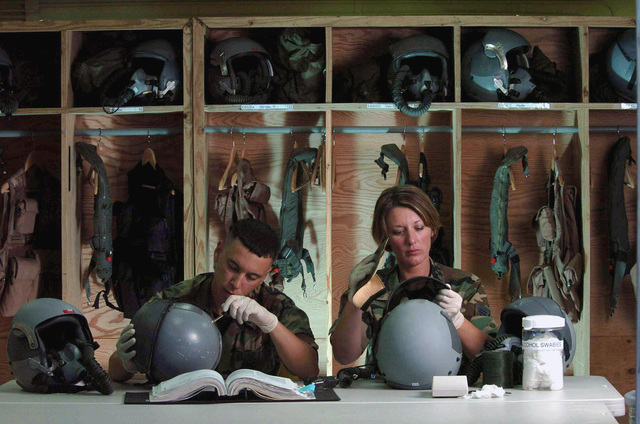 At Andersen Air Force Base (AFB), Guam (GU), US Air Force (USAF) STAFF Sergeant (SSGT) Terilyn Morrison (right) and AIRMAN (AMN) Felipe Maymi-Baez, both life support technicians with the 5th Bomb Wing (BW), Minot Air Force Base (AFB), North Dakota (ND), inspect helmets belonging to B-52 Stratofortress bomber aircraft aircrew members