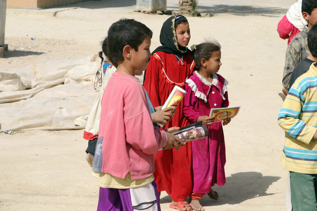 These local Iraqi school children hold pamphlets given to them by US Marine Corps (USMC) Marines, Headquarters and Service Company (H&S Co), 2nd Battalion (BN), 7th Marine Regiment (2/7th MAR), 1ST Marine Division (MARDIV), and US Army (USA) Soldiers, Psychological Operations (PSYOPS), attached to the 1ST MARDIV, warning all Iraqi children not to point any type of weapon at a US or Coalition soldier. This pamphlet distribution operation was conducting during a USMC and USA official civil affairs visit to a primary school located along Alternate Supply Route (ASR) Bronze near the town of Hit, Al Anbar Province, Iraq (IRQ), as they participate in a Security and Stabilization Operation...