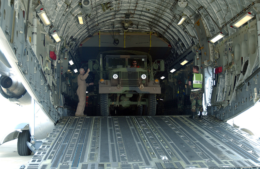 A US Air Force (USAF) loadmaster (left) uses hand signals to guide a USAF M35A1/A2 Series 2-1/2 ton (Deuce and a Half) cargo truck as it backs-up into the cargo bay of a C-17A Globemaster III cargo aircraft during Phase I of an Operational Readiness Exercise (ORE) being conducted at Shaw Air Force Base (AFB), South Carolina (SC)