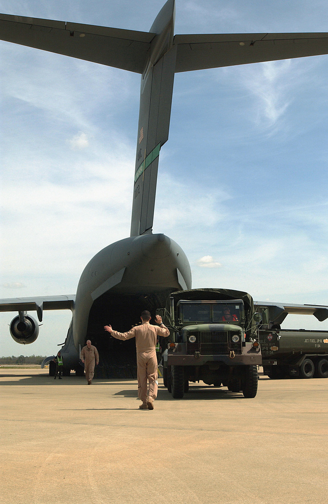 A US Air Force (USAF) loadmaster uses hand signals to guide a USAF M35A1/A2 Series 2-1/2 ton (Deuce and a Half) cargo truck as it backs-up and pushes the M-200 generator it is towing into the open cargo bay of a C-17A Globemaster III cargo aircraft during Phase I of an Operational Readiness Exercise (ORE) being conducted at Shaw Air Force Base (AFB), South Carolina (SC)
