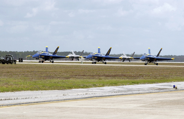 Three US Navy (USN) Blue Angels F/A-18 Hornet fighter and attack aircraft (foreground) and two US Air Force (USAF) F/A-22A Raptor fighter and attack aircraft (background) sit parked in preparation to take-off from Tyndall Air Force Base (AFB), Florida (FL), during the Gulf Coast Salute, which is Tyndall AFBs annual open house and air show