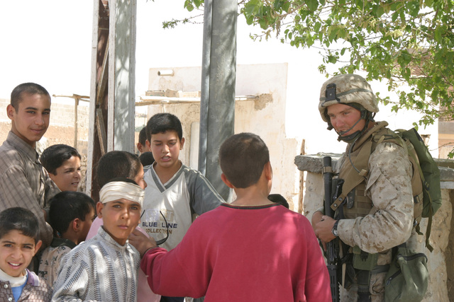 US Marine Corps (USMC) Lance Corporal (LCPL) John Richardson (right), Kilo Company (K Co), 3rd Battalion (BN), 4th Marine Regiment (3/4th MAR), 1ST Marine Division (MARDIV), speaks with several local Iraqi boys in the city of Haqlaniyah, Al Anbar Province, Iraq (IRQ), as he participates in a Security and Stabilization Operation (SASO) in the area in support of Operation IRAQI FREEDOM