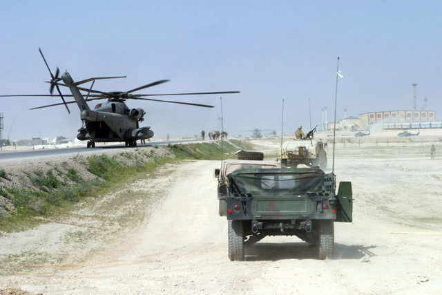 A US Marine Corps (USMC) 1ST Marine Division (MARDIV) motorized unit (right) moves into position to provide security as a USMC CH-53E Helicopter (left), transporting USMC Lieutenant General (LGEN) James T. Conway, Commanding General (CG), I Marine Expeditionary Force (MEF), and USMC Major General (MGEN) James N. Mattis, Commanding General (CG), 1ST MARDIV, sits on a landing zone (LZ) at Forward Operating Base (FOB) Camp Al Qaim (Qaim), Al Anbar Province, Iraq (IRQ), during Operation IRAQI FREEDOM