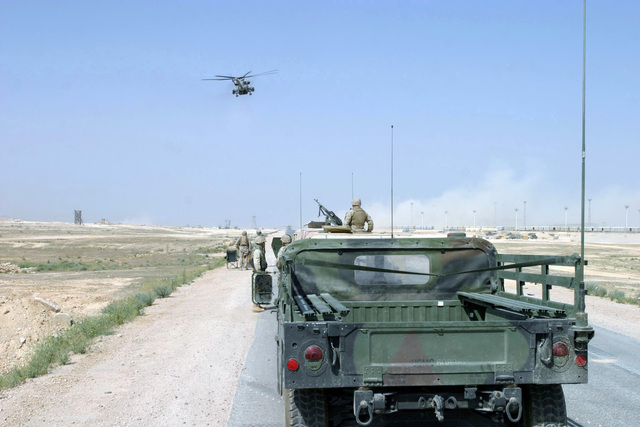 A US Marine Corps (USMC) 1ST Marine Division (MARDIV) motorized unit stands security as a USMC CH-53E Helicopter (background), transporting USMC Lieutenant General (LGEN) James T. Conway, Commanding General (CG), I Marine Expeditionary Force (MEF), and USMC Major General (MGEN) James N. Mattis, Commanding General (CG), 1ST MARDIV, prepares to land at Forward Operating Base (FOB) Camp Al Qaim (Qaim), Al Anbar Province, Iraq (IRQ), during Operation IRAQI FREEDOM