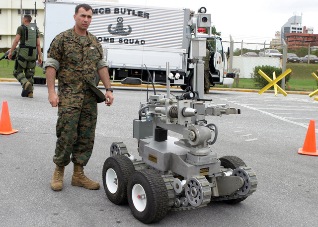 US Marine Corps (USMC) Sergeant (SGT) Ken Blankenship (left), Explosive Ordnance Disposal (EOD) Technician, assigned to Headquarters Company, 9th Engineer Support Battalion (ESB), 3rd Force Service Support Group (FSSG), sets up a Remote Ordnance Neutralization System (RONS) robot during a Force Protection Exercise (FPEX) being conducted at Camp Smedley D. Butler, Okinawa, Japan