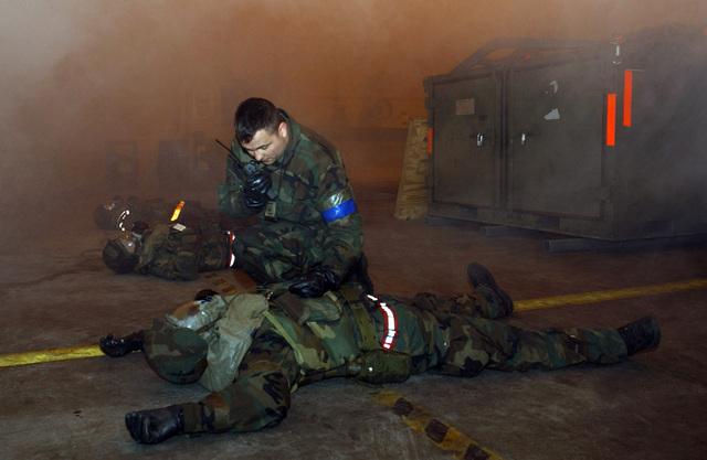 US Air Force (USAF) STAFF Sergeant (SSGT) Michael Funk of the 3rd Aircraft Maintenance Squadron (MXS), 90th Aircraft Maintenance Unit Elmendorf Air Force Base (AFB), Alaska (AK), calls in simulated casualties after a post attack assessment in support of the 3rd Wing's Operational Readiness Inspection (ORI)