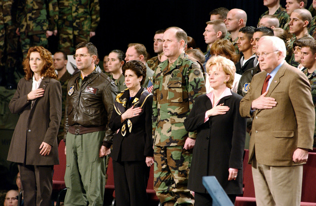 US Vice President Richard Cheney (right), Mrs. Lynne Cheney, US Army (USA) Major General (MGEN) John M. Brown III, Commander, US Army Alaska, Fort Richardson, Mrs. Brown, US Air Force (USAF) Colonel (COL) Michael A. Snodgrass, Commander, 3rd Wing, Elmendorf Air Force Base (AFB), Dr. Bobbi Snodgrass, give respect during the singing of the national anthem. US Vice President Cheney stopped in at Elmendorf AFB to give a speech to the troops of Elmendorf and the neighboring USA post Fort Richardson, on his way to Asia to visit 11 countries