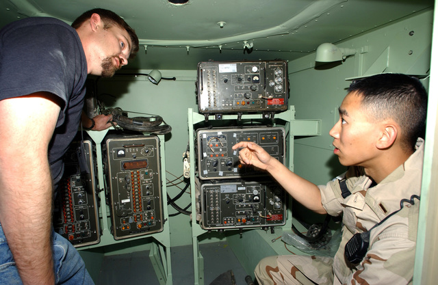 Joseph Taylor (left), contractor, 407th Expeditionary Communications Squadron (ECS), explains the functions of the Tactical Air Navigation System to US Air Force (USAF) Second Lieutenant (2LT) Louis T. Wong, 407 Expeditionary Communications Squadron (ECS). The navigation system is a line-of-sight, beacon-type, air navigation aid that provides slant range, bearing, and identification information. Aircraft are able to determine their position in relationship to Tallil Air Base, Iraq