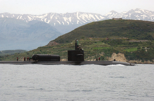 The US Navy (USN) Los Angeles Class Attack Submarine USS DALLAS (SSN 700) arrives in Souda Bay's harbor for a brief port visit. Commissioned in 1981, Dallas is the first Los Angeles-class submarine to have a Dry Deck Shelter (DDS), shown on the submarine's back. Dry Deck Shelters provide specially configured nuclear powered submarines with a greater capability of deploying Special Operations Forces (SOF). DDSs can transport, deploy, and recover SOF teams from Combat Rubber Raiding Crafts (CRRC) or SEAL Delivery Vehicles (SDV), all while remaining submerged. In an era of littoral warfare, this capability substantially enhances the combat flexibility of both the submarine and SOF personnel