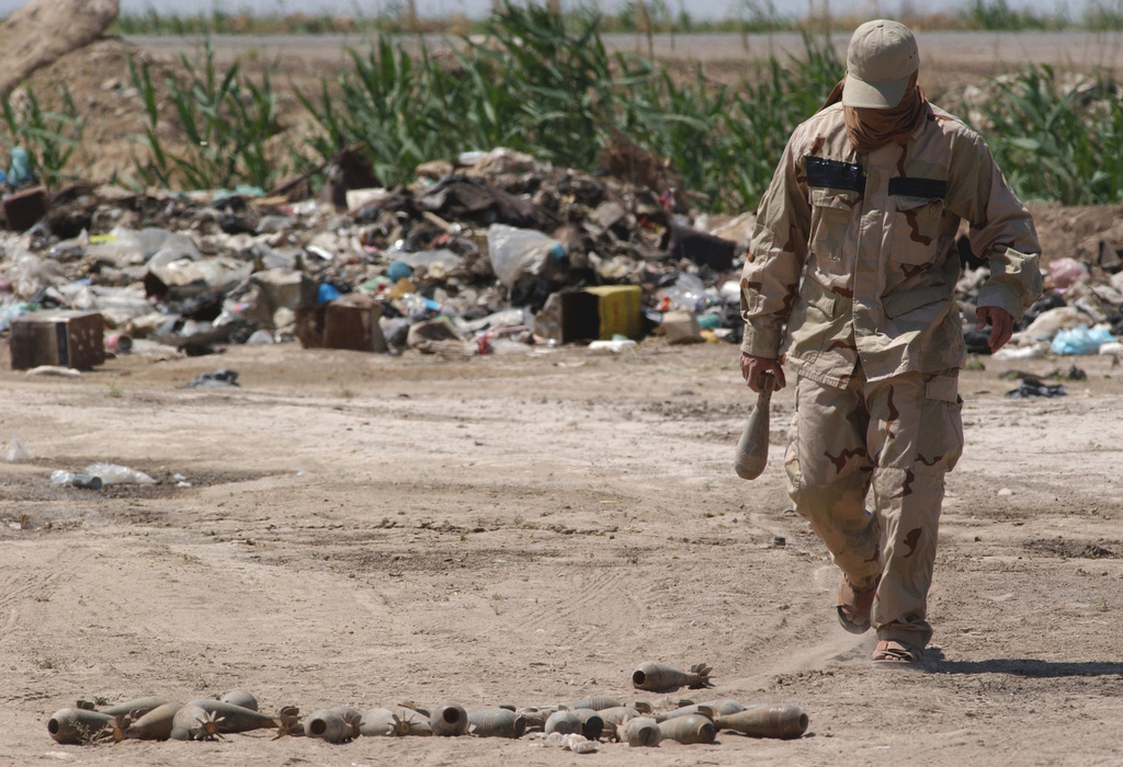 A local Iraqi citizen helps to stockpile 82mm mortar rounds