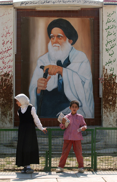 Iraqi school children standing by an Iraqi religious elder shrine in Sadr City, Iraq (IRQ), during Operation IRAQI FREEDOM
