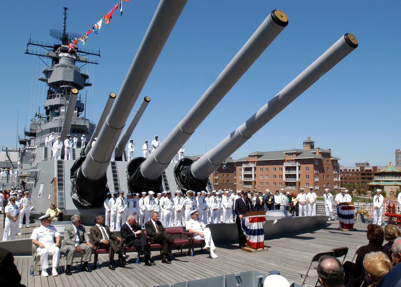 US Senator, The Honorable John Warner, (R-VA) (center), stands beneath the 16-inch guns on the deck of the decommissioned US Navy (USN) Battleship, WINCONSIN (BB 64), and addressed the gathering during a 60th Anniversary Celebration held at Hampton Roads Naval Museum, Norfolk Virginia (VA). Seated to his immediate right is USN Rear Admiral (RADM) (lower-half) Stephen Turcotte, Commander, Mid-Atlantic Region
