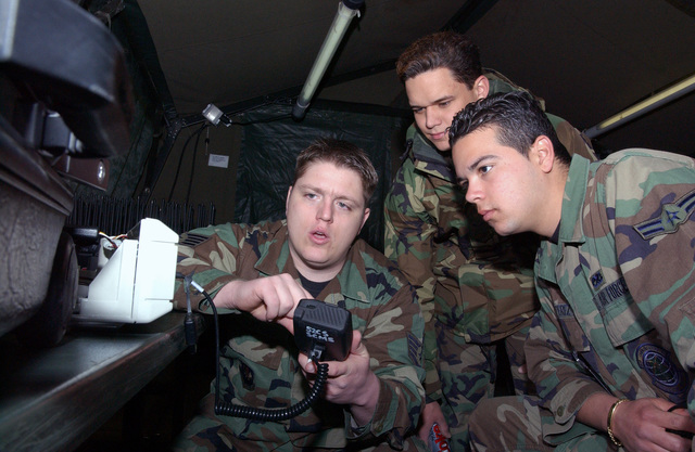 US Air Force (USAF) STAFF Sergeant (SSGT) Jeffery Hartman (left) teaches USAF AIRMAN First Class (A1C) Travis Hoisington (center) and USAF A1C Edward Perez, Ground Radio Technicians, 52nd Communications Squadron (CS), how to load type 2 digital encryption codes into the Land Mobil Base Station. The Airmen are preparing for the 52nd Fighter Wing (FW) exercise Harley Saber at Spangdahlem Air Base (AB), Germany (DEU)