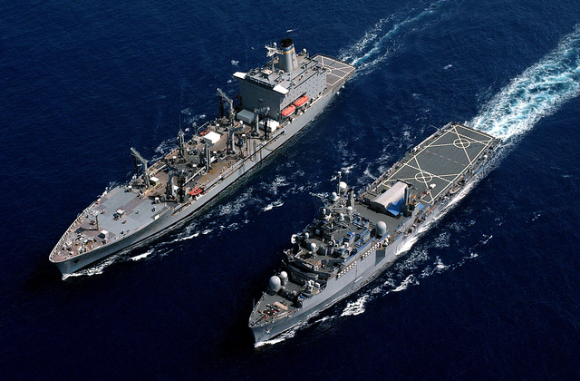 Aerial view of the US Navy (USN) CONVERTED AUSTIN CLASS: MISCELLANEOUS COMMAND SHIP: USS CORONADO (AGF 11) (left) and the USN Military Sealift Command Ship (MSC), HENRY J. KAISER CLASS: OILER, USS TIPPECANOE (T-AO 199), underway side-by-side while conducting Underway Replenishment (UNREP) operations in the Pacific Ocean