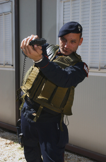 """Luciotti Dania, Italian Air Force Carabinieri, armed with a 9 mm M9 Pistol, participates in the """"Splicing Pie"""" training during a weeklong Joint Tactics course developed to establish a better working relationship between members of the US Air Force (USAF) Office of Special Investigations (OSI), the 31st Security Forces Squadron (SFS), and the Italian Air Force Carabinieri"""