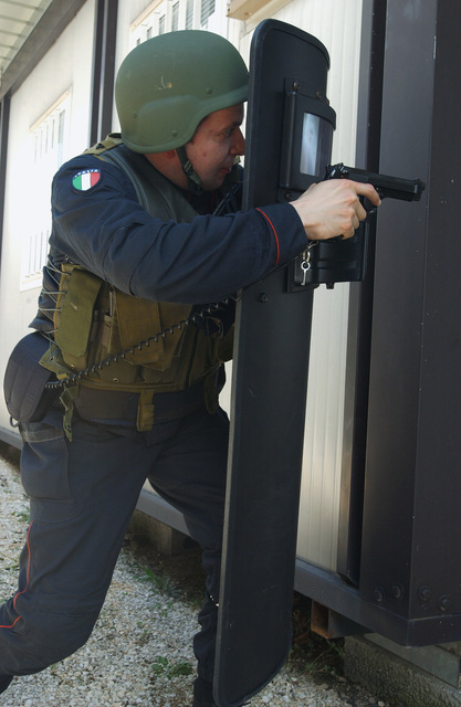 """Morassut Luca, Italian Air Force Carabinieri, uses a shield and 9 mm M9 Pistol as part of """"Splicing Pie"""" training during a weeklong Joint Tactics course developed to establish a better working relationship between members of the US Air Force (USAF) Office of Special Investigations (OSI), the 31st Security Forces Squadron (SFS), and the Italian Air Force Carabinieri"""