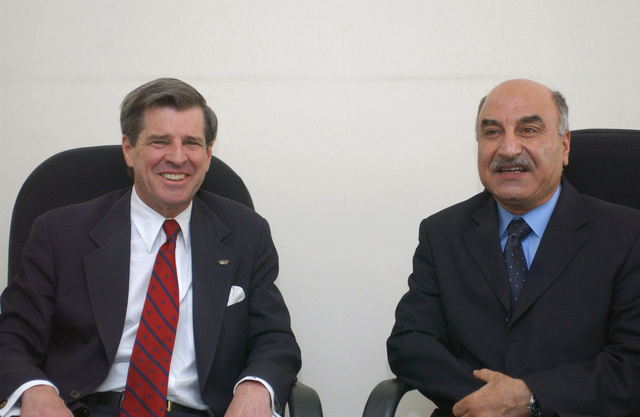 US Ambassador to Iraq, The Honorable Paul Bremer (left) and Dr. Rashad Mandan Omar, Iraqi Minister of Science and Technology, enjoy a few laughs after their speeches at Baghdad University