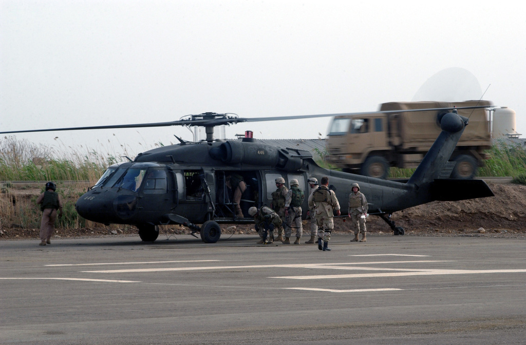 US Military Personnel assigned to the Chemical Biological Intelligence Survey (CBIS) Team, prepare to board a US Army (USA) UH-60 Black Hawk helicopter at Camp Victory, Baghdad, Iraq. The Team will investigate suspected chemical agents found on a chicken farm 10-kilometers Northeast of Fallujah, Iraq during Operation IRAQI FREEDOM