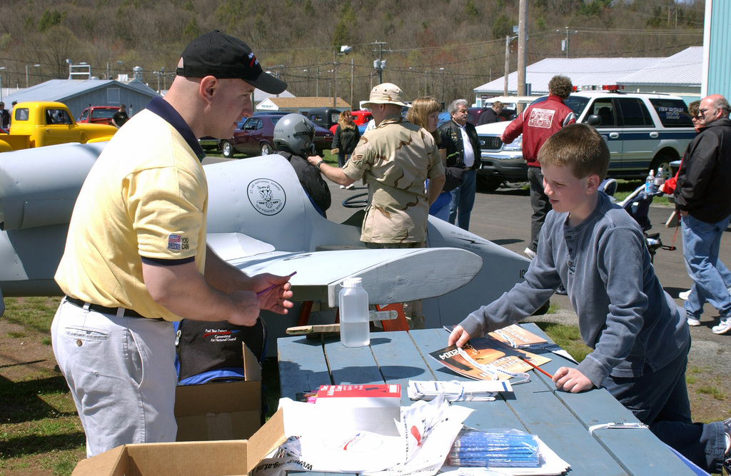 US Air Force (USAF) STAFF Sergeant (SSGT) William Deme (foreground left) mans a display booth for the Connecticut Air National Guard (CTANG), during the Summer Knights car show and swap meet, held at Bradley Air National Guard Base (ANGB) Berlin, Connecticut (CT). The program donates contributions for families of deployed service men and women, of the Connecticut Army National Guard (CTARNG) and the CTANG