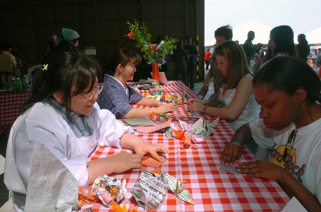Members of the Yokota Air Base (AB) Community try to master the skill of making Origamis by watching their Japanese Instructors, during the 2nd Annual Japanese Cultural event held at, Yokota Air Base (AB), Japan. Origami is the art of turning a simple piece of paper into a piece of art that resembles a bird, and is one of the many things to learn and participate in during the event