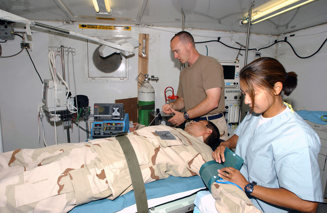 US Air Force (USAF) Captain (CPT) Michelle Olarte and Captain (CPT) Aaron Holloway, with the 4077th Emergency Medical Group (EMG), attend to SSGT Johannes Oribello, from the 4077th EMG, while he acts out the part of an injured victim during a mass casualty exercise at Tallil Air Base (AB), Iraq (IRQ),in support of Operation IRAQI FREEDOM