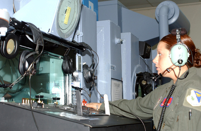 A US Air Force (USAF) decompression chamber technician looks in and checks instrument dials while the Class of 05-09 is in the chamber training