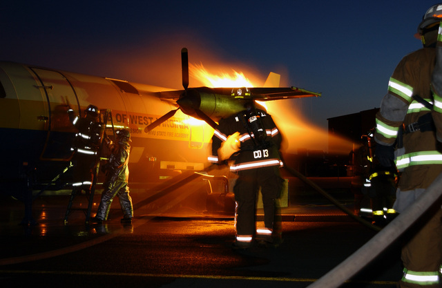 At the aircraft fire simulator firefighters spray down the engine fire as other firefighter enter the aircraft during a live fire training session held at the 167th Air Wing (AW), West Virginia Air National Guard (WVANG), Martinsburg, West Virginia (WV). The training is a West Virginia University (WVU) program designed to provide required Federal Aviation Administration (FAA) annual training
