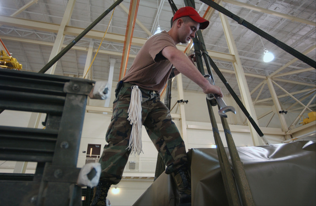 US Army (USA) Private First Class (PFC) Matthew Mendel, 782nd Main Support Battalion, 82nd Airborne Division (AD), tightens two point links that will support the weight of a High-Mobility Multipurpose Wheeled Vehicle (HMMWV) under a canopy at Fort Bragg, North Carolina (NC)