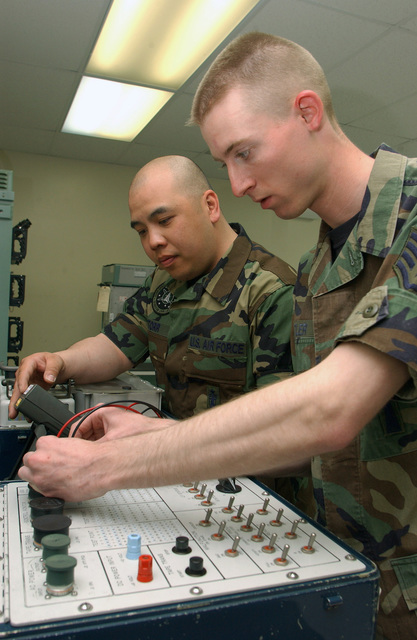 """US Air Force (USAF) STAFF Sergeant (SSGT) Landon Cutler (right) with the 91st Space Wing (SW) """"Roughriders,"""" Minot Air Force Base (AFB), North Dakota (ND), works on equipment, while SSGT Ananh Torr assists during the Electronics Laboratory Event at Vandenberg Air Force Base (AFB), California (CA). Guardian Challenge, the world's premier space and missile competition, is a four-day event hosted annually at Vandenberg AFB"""