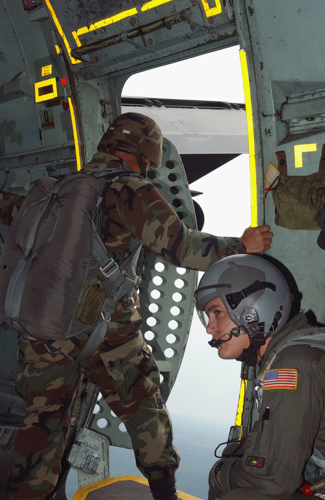 As Loadmaster US Air Force (USAF) Technical Sergeant (TSGT) Jose Chaudez looks on, a US Army (USA) Jumpmaster makes a visual safety check at a C-141 Starlifter cargo transport aircraft open troop door, in preparation for a parachute jump out over a Fort Benning Georgia (GA) drop zone