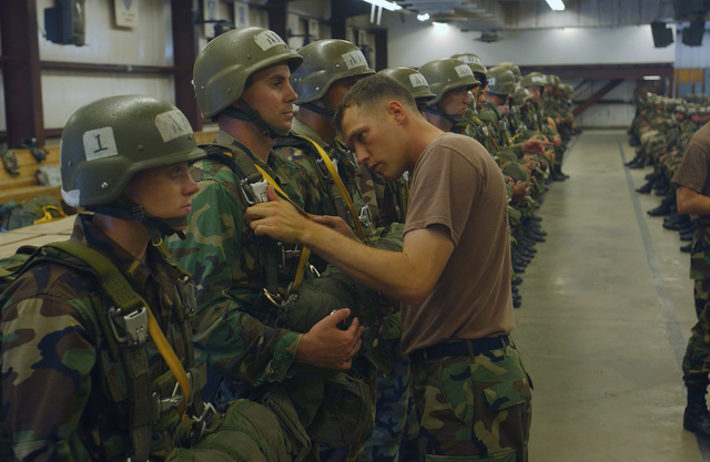 US Army (USA) students from the Airborne School at Fort Benning, Georgia (GA), are inspected by their jump masters prior to their first airdrop mission