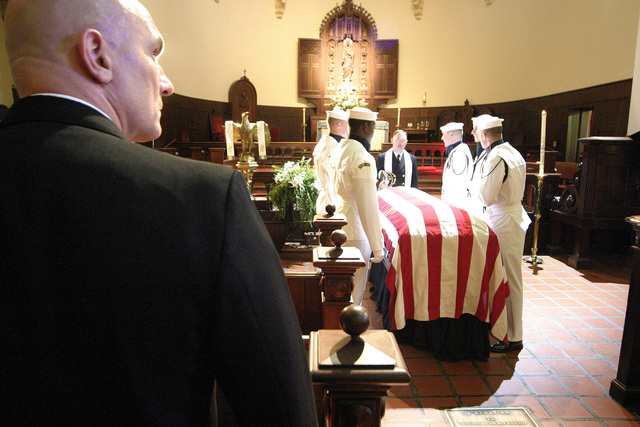 """US Navy (USN) Lieutenant Commander (LCDR) Gregory Barringer (foreground), observes as Sailors assigned to a Ceremonial Honor Guard Team and Captain (CPT) James Fisher (background center), USN, Chaplain, are filmed for an episode of the """"The West Wing"""" television show, inside the historic St. Anne's Church, located in Annapolis, Maryland (MD)"""