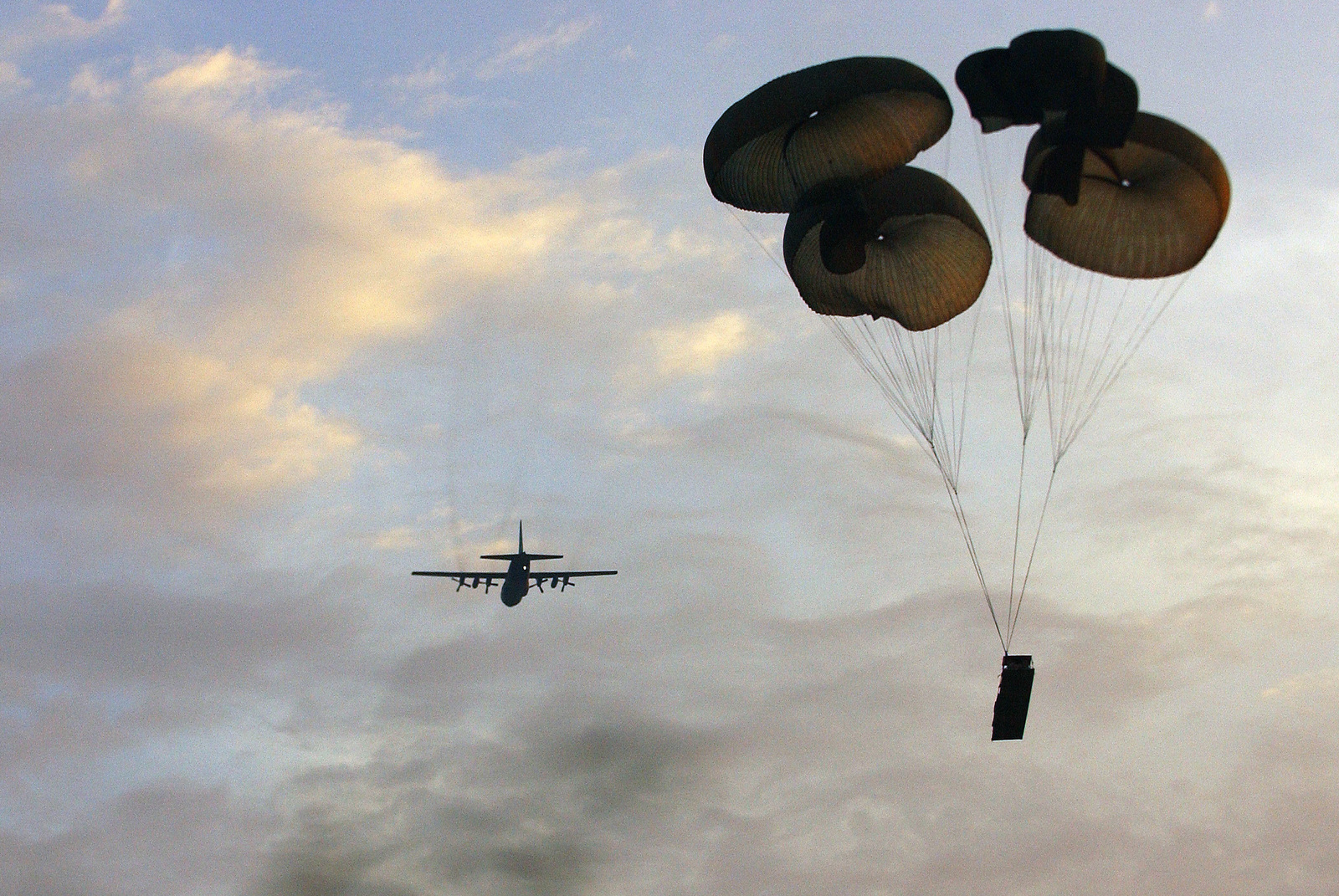 A US Air Force (USAF) C-130 Hercules cargo aircraft drops an M198 Towed Howitzer 105 mm cannon onto drop zone Holland at Fort Bragg, North Carolina (NC), in support of exercise Large Package week. Large Package Week is a joint US Army and US Air Force airdrop, designed to enhance service cohesiveness. (SUBSTANDARD)