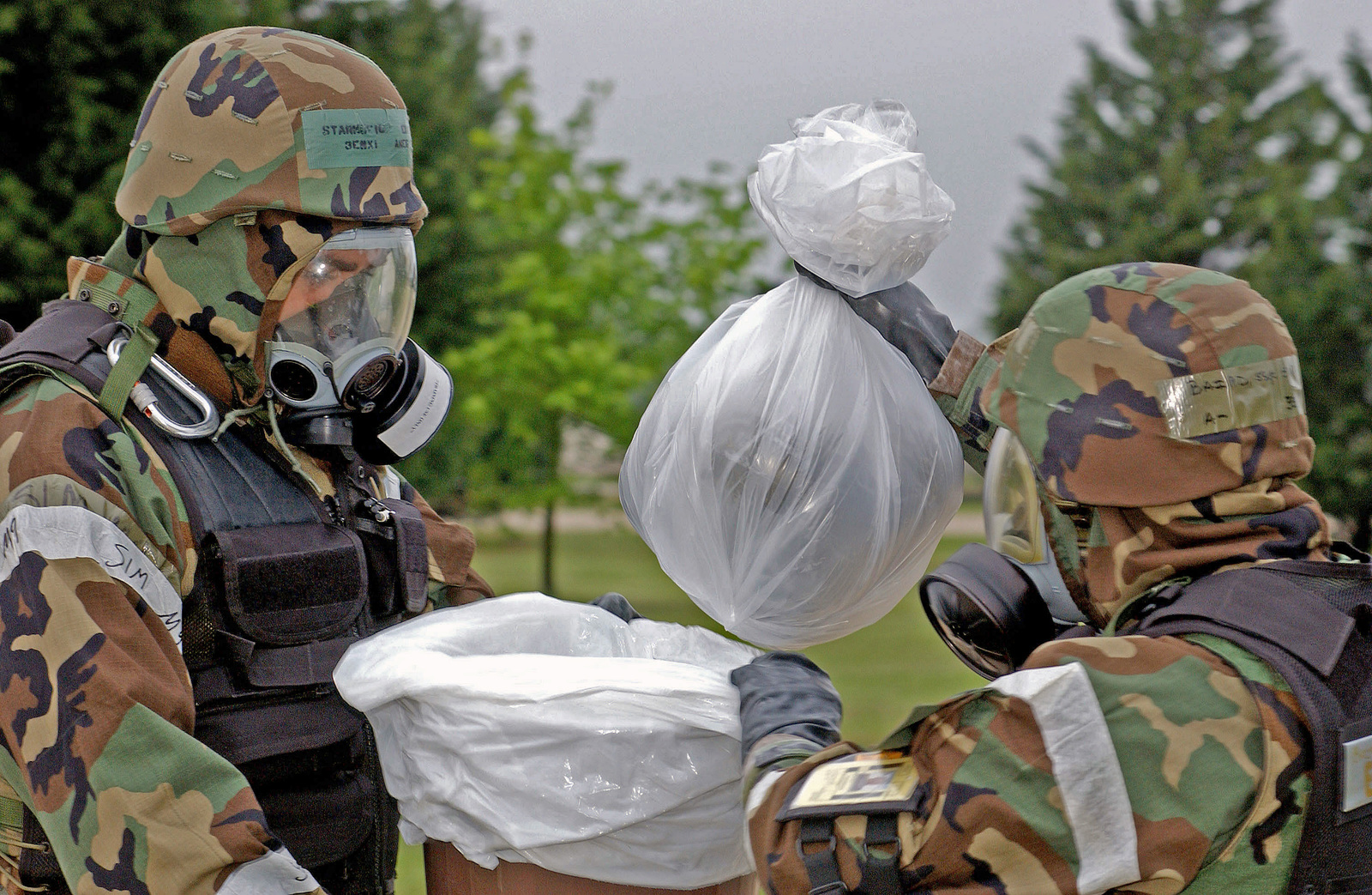 Dressed in Mission-Oriented Protective Postures level-4 (MOPP-4) gear, US Air Force (USAF) SENIOR AIRMAN Anton Starkovich (left) and STAFF Sergeant (SSGT) William Baird bag a simulated unexploded ordnance in order to dispose of it, during a Tactical Evaluation at Royal Air Force (RAF) Lakenheath, England (ENG)