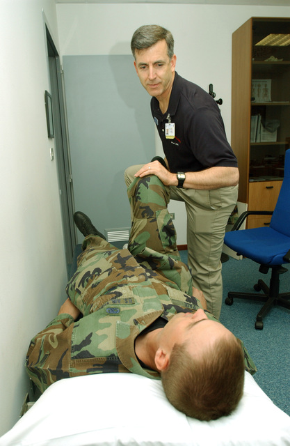 US Air Force (USAF) Major (MAJ) Charles Houlding, a Physical Therapist with the 31st Aeromedical Squadron (AS) at Aviano Air Base (AB), Italy (ITA), works on SENIOR AIRMAN (SRA) Matthew Pace, a Calibration Technician who has been experiencing back pain since a car wreck two years ago