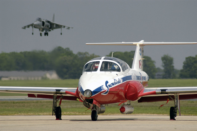 A Canadian Forces Air Command CT-114 Tutor basic pilot training aircraft assigned to the 431 Squadrons Aerial Demonstration Team Snowbirds taxies on the flight line during the Joint Service Open House Celebration held at Andrews Air Force Base (AFB), Maryland (MD). A US Marine Corps (USMC) AV-8B Harrier II aircraft, assigned to Marine Attack Squadron Two Three One (VMA-231), performs a hovering maneuver in the background