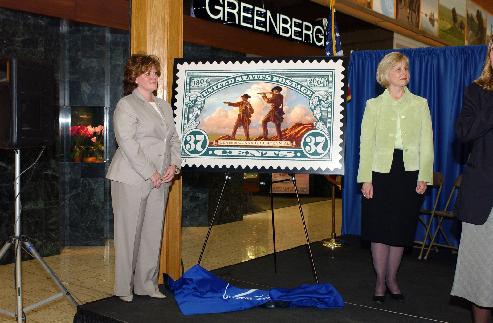 Susan LaChance (left), of the United States Postal Service (USPS) along with a representative from the Iowa Governors Office unveil one of three new stamps honoring US Army (USA) Captain (CPT) Meriwether Lewis and CPT William Clark, the leaders of the 1804-1806 Lewis and Clark expedition. The stamps were simultaneously unveiled in 11 states along the trail of the expedition. Sioux City, Iowa is where Sergeant Floyd, the only person to die on the expedition, is buried