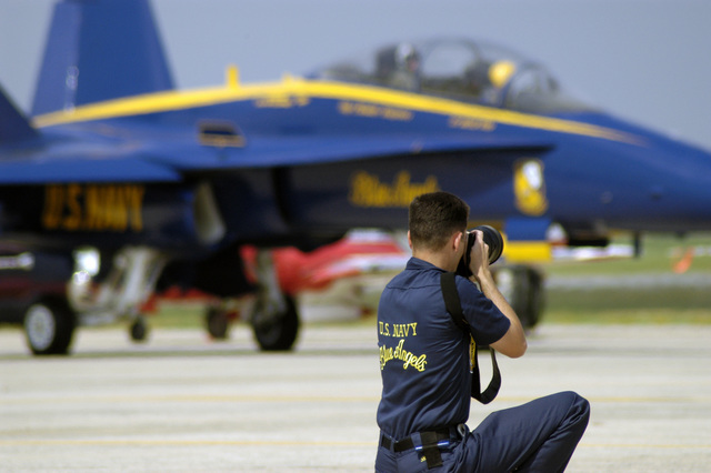 US Navy (USN) Illustrator Draftsman (DM) CHIEF PETTY Officer Second Class (CPO2) Jeffrey Ballge, assigned as a photographer to the USN Blue Angels, flight demonstration team, photographs one of the teams F/A-18A Hornet aircraft as it taxis to the active runway during the Joint Service Open House Celebration held at Andrews Air Force Base (AFB), Maryland (MD). The open house showcased civilian and military aircraft and provided many flight demonstrations and static displays