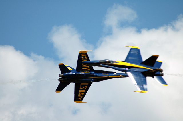 Two US Navy (USN) Blue Angels F/A-18C Hornet aerial demonstration team aircraft perform a close scissors-cross maneuver during the Joint Service Open House Celebration, held at Andrews Air Force Base (AFB), Maryland (MD). The open house showcased civilian and military aircraft and provided many flight demonstrations and static displays