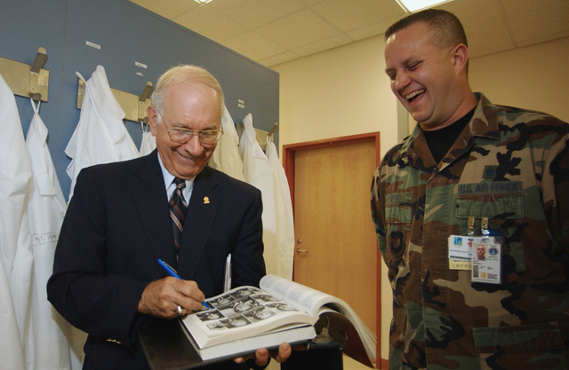 Retired CHIEF MASTER Sergeant of the Air Force (CMSAF) Sam E. Parish (left) signs a Promotion Fitness Examination book for US Air Force (USAF) MASTER Sergeant (MSGT) Samuel Byrd, Non-Commissioned Officer in Charge (NCOIC) of Laboratory Services, 48th Medical Support Squadron (MDSS) 48th Fighter Wing (FW), Royal Air Force (RAF) Lakenheath, United Kingdom, during a recent visit to the base. CHIEF Parish was the 8th CMSAF and served from August 1983 until 1986