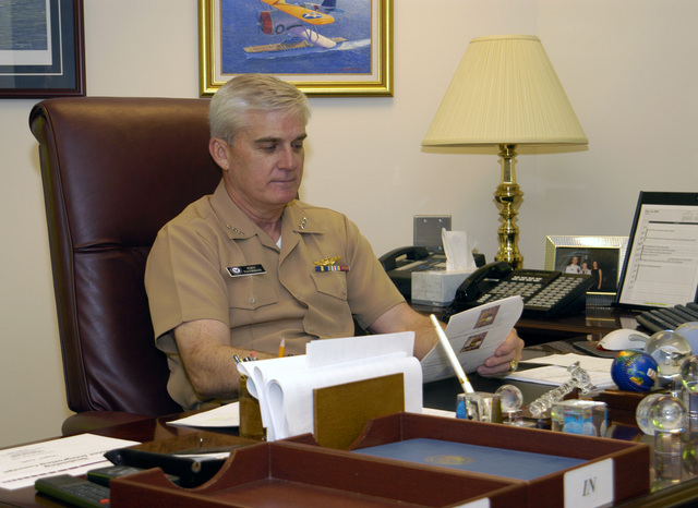 US Navy (USN) Vice Admiral (VADM) John B. Nathman, Deputy CHIEF of Naval Operations, (Warfare Requirements and Programs) (N6/N7), conducts morning business at his desk in his Pentagon Office