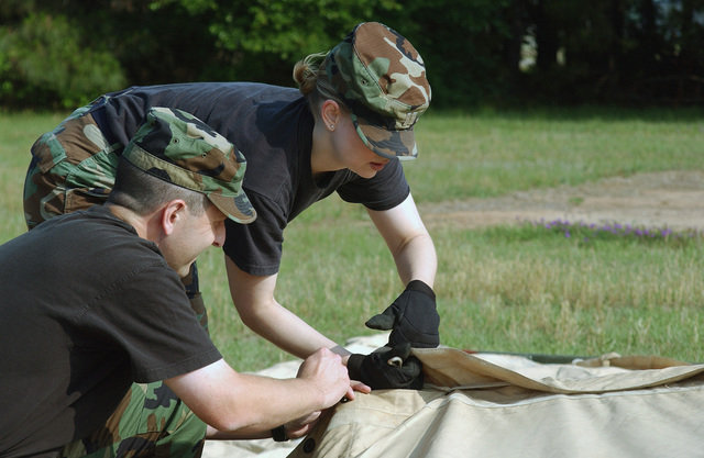 """US Air Force (USAF) Lieutenant Colonel (LTC) Gary Brown (foreground), and USAF Captain (CPT) Rebecca Tatum, CHIEF of Operations Law, both assigned to the 20th Fighter Wings Judge Advocate Generals (JAG) prepare for field operations law training by helping to set up a """"temper"""" tent at Shaw Air Force Base, South Carolina (SC)"""