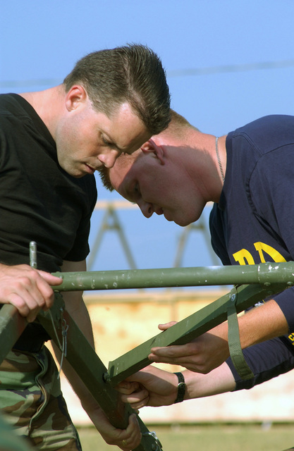 """US Air Force (USAF) Technical Sergeant (TSGT) Chuck Stewart (foreground), Claims Non-commissioned Officer in Charge (NCOIC), and a AIRMAN from the 20th Civil Engineering Squadron (CES), prepare for field operations law training by helping to set up a """"temper"""" tent at Shaw Air Force Base, South Carolina (SC)"""