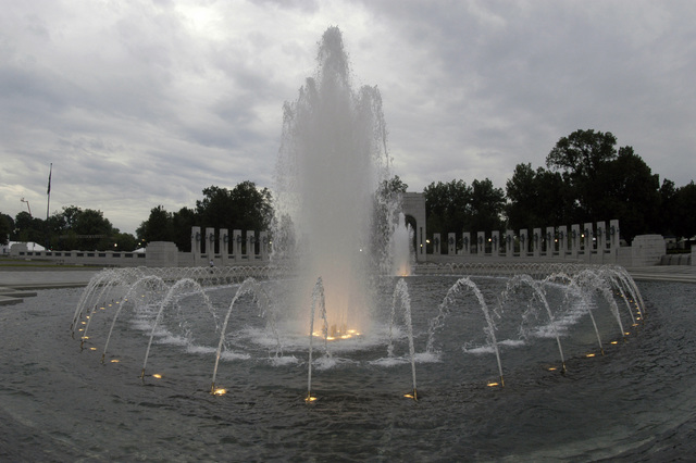 At twilight, the illuminated fountains of the newly completed National World War II Memorial, in the Washington, District of Columbia, established by the American Battle Monuments Commission, honoring military veterans of World War II